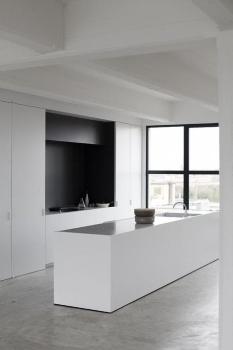a minimalist black and white kitchen with a matte backsplash and a black hood, a long kitchen island with a shiny countertop