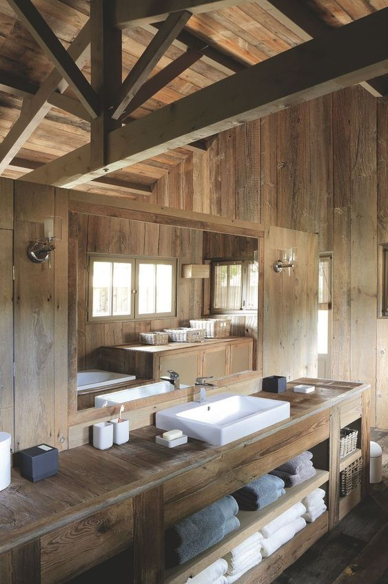 a minimalist chalet bathroom all clad with light-colored wood, with a sink and a large wooden vanity