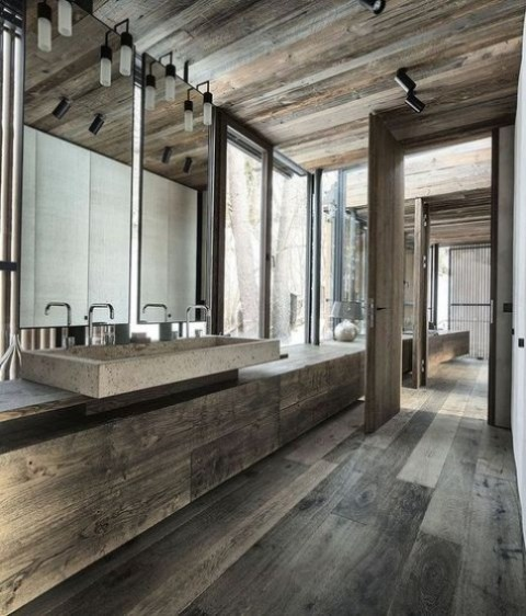 a minimalist chalet bathroom clad with dark weathered wood, with a stone sink, large windows and lamps