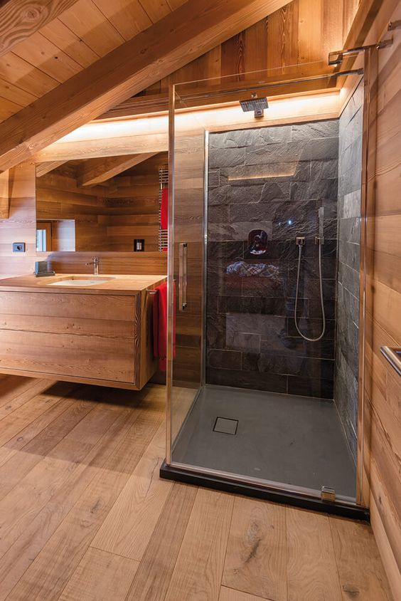 a minimalist chalet bathroom clad with light-colored wood, with a shower space done with stone tiles and built-in lights
