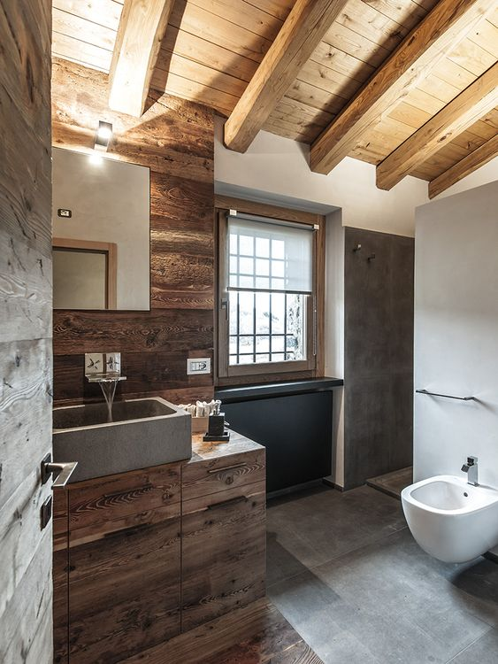 a minimalist chalet bathroom done with wood, grey tiles and concrete, modern appliances and a window for a cool view