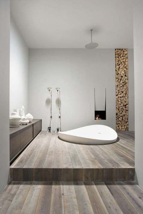 a minimalist chalet bathroom with white walls, a reclaimed wooden floor, a built-in tub, a fireplace and a firewood storage
