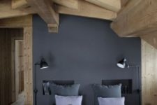 a minimalist chalet bedroom with a black statement wall, grey bedding, a faux fur bedspread and wooden beams