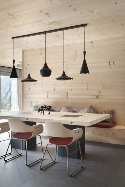 a minimalist chalet dining room clad with light-colored wood, with an arrangement of black lamps, a table and chair plus plaid pillows