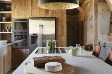 a minimalist chalet kitchen done with sleek wood, with a large kitchen island, a black lamp and a stone countertop