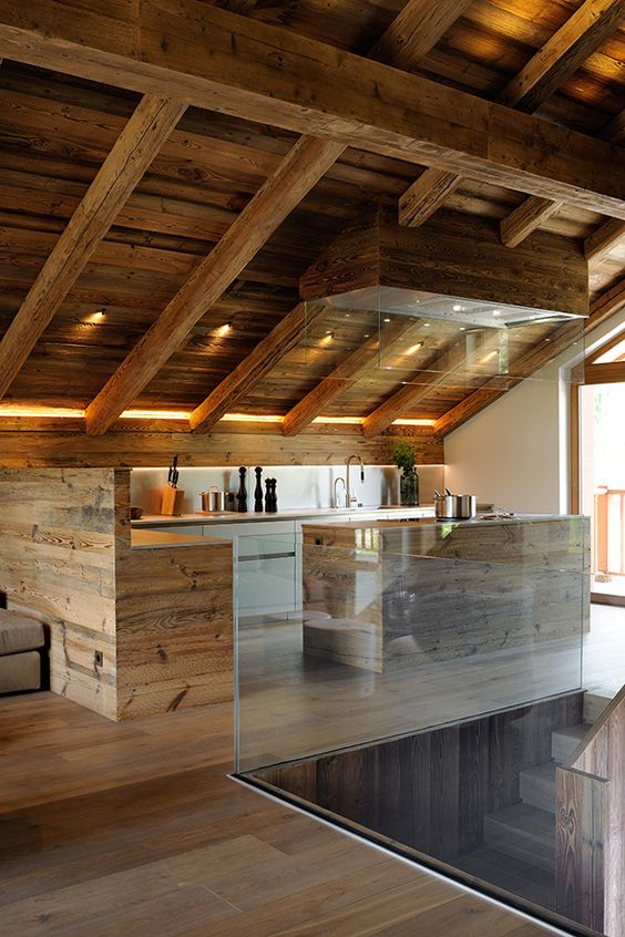 a minimalist chalet kitchen done with sleek wooden cabinets, a small kitchen island, a large hood with lights and built in lights