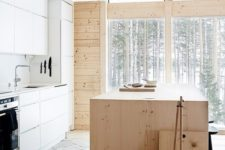 a minimalist chalet kitchen with a plywood kitchen island, sleke white cabinets and a stone floor flooded with natural light