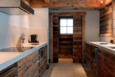 a minimalist chalet kitchen with wooden cabinets, white concrete countertops, metal appliances and a black ceiling