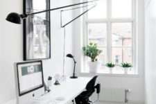 a minimalist double home office with a long desk, black chairs, an artwork and a long sconce