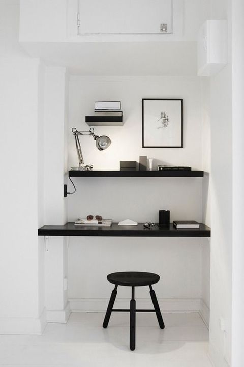 a minimalist home office nook in white, with black shelves and a floating desk, a lamp, artworks and a black chair