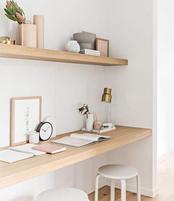 a minimalist home office nook with a shelf and a built-in desk, white stools, some blooms and a brass lamp