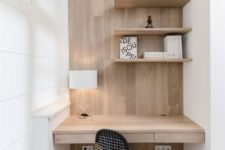 a minimalist home office nook with some shelves, a built-in desk and a black chair plus a lamp
