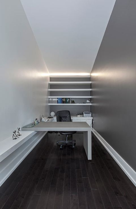 a minimalist home office with a grey accent wall, white furniture and open shelves plus built in lights