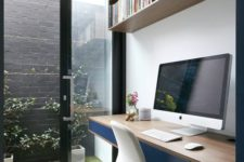 a minimalist home office with an open shelf, a desk with navy drawers, a white chair and a small courtyard