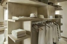 a minimalist makeshift closet made of light-colored wood, with lots of shelves and a holder for hangers