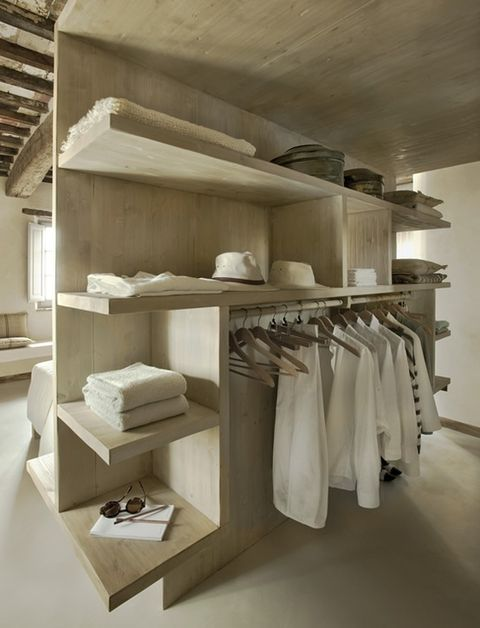 a minimalist makeshift closet made of light colored wood, with lots of shelves and a holder for hangers
