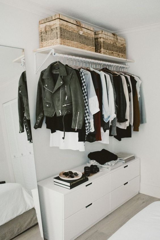 a minimalist makeshift closet with a holder for hangers, wicker boxes, a white sideboard for small stuff