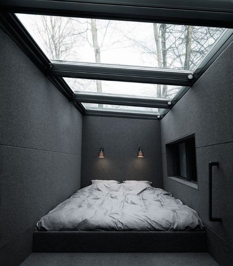 a minimalist masculine bedroom with dakr walls, a glazed ceiling and a bed plus sconces to look at the sky