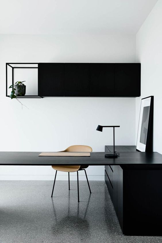 a minimalist monochromatic home office with a large black desk, a storage unit on the wall, a lamp and an artwork