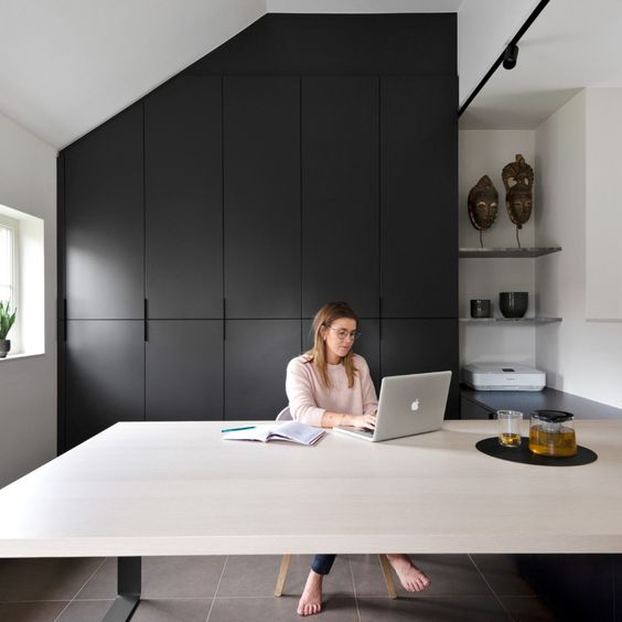 a minimalist monochromatic home office with a large black storage unit, a large desk and some open shelves