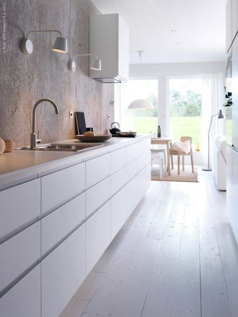 a minimalist narrow white kitchen with long cabinets, with a catchy rough concrete wall and white countertops