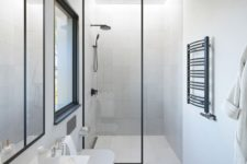 a minimalist neutral bathroom with tiles, a white vanity, a mirror, a window and a shower space plus black touches for drama