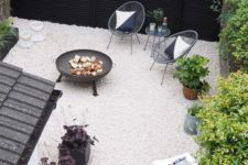 a minimalist patio with black wicker chairs, a black fire bowl, a coffee table and some greenery in pots