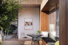 a minimalist terrace wiht a built-in bench, colorful pillows, a black table and chairs