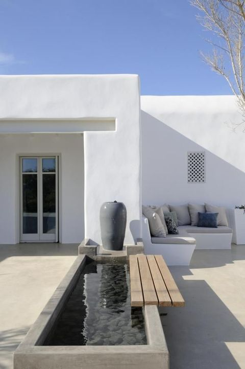 a minimalist terrace with a built in bench with pillows, a water body with pebbles and a mini built in bench