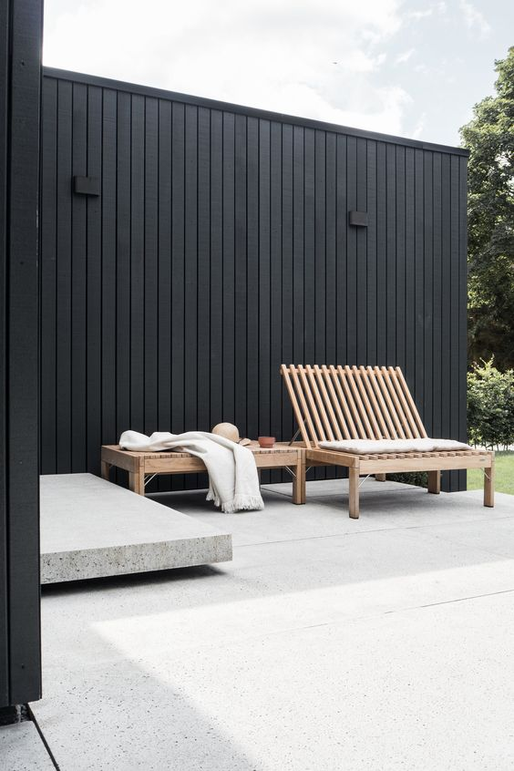 a minimalist terrace with a concrete bench, a wooden bench and lounger is very stylish