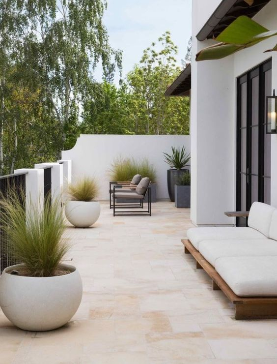 a minimalist terrace with a couple of chairs, a comfy outdoor sofa and statement planters with greenery
