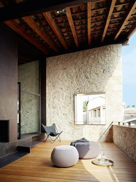 a minimalist terrace with a deck, a built-in fireplace, grey minimal furniture and a mirror
