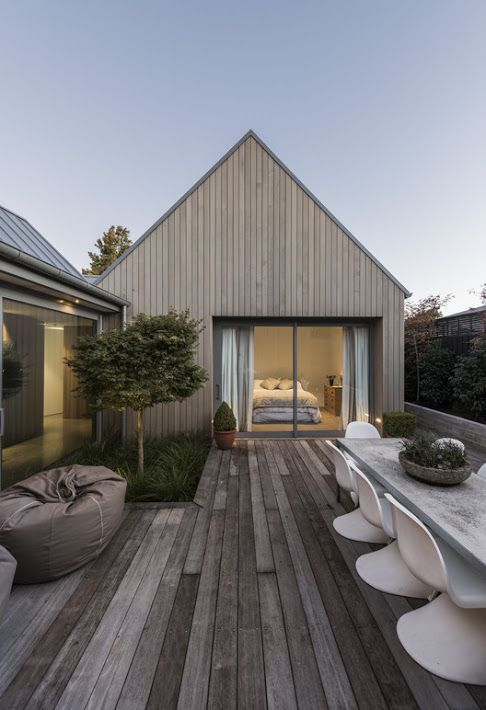 a minimalist terrace with a reclaimed wooden deck, beanbag chairs, grass and a tree, a concrete table and plastic chairs