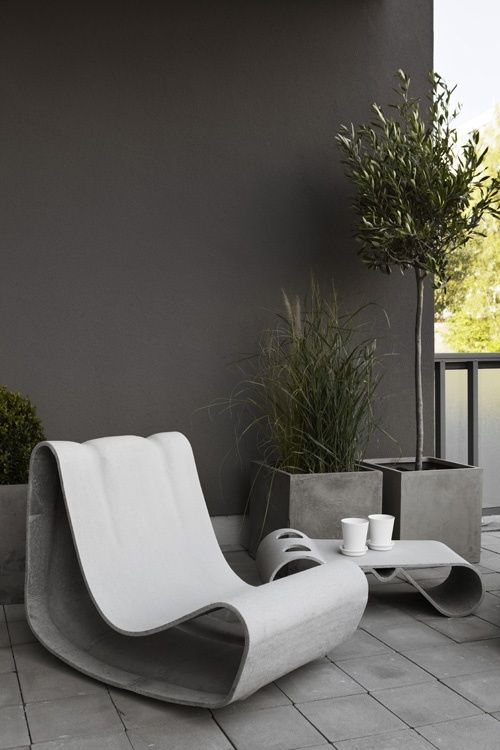 a minimalist terrace with a tiled floor, concrete chairs, a coffee table and planters with greenery