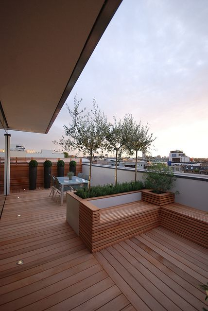 a minimalist terrace with a wooden deck, a dining space, built in wooden furniture and growing greenery and trees