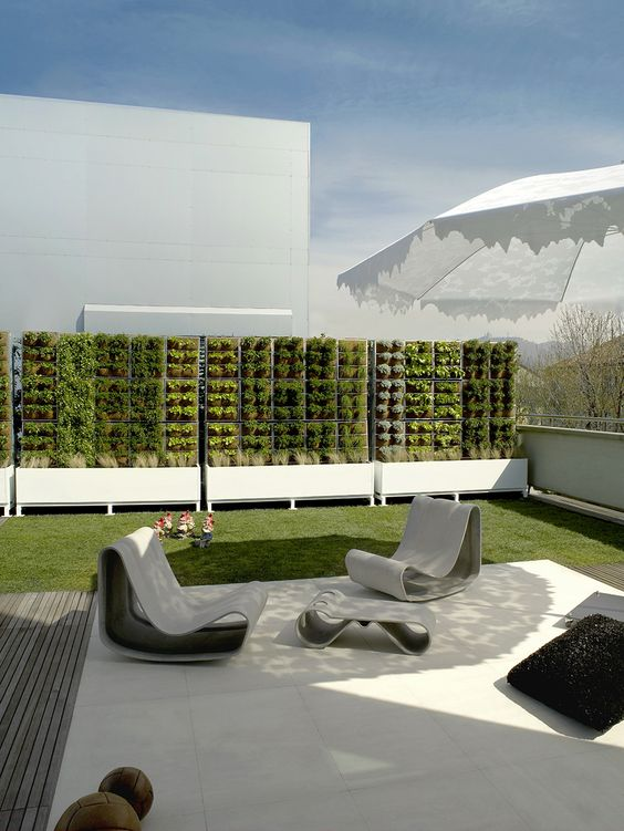a minimalist terrace with catchy white concrete furniture, a deck, a green lawn and pillows