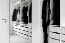 a minimalist white closet with built-in drawers, open storage compartments and a large mirror