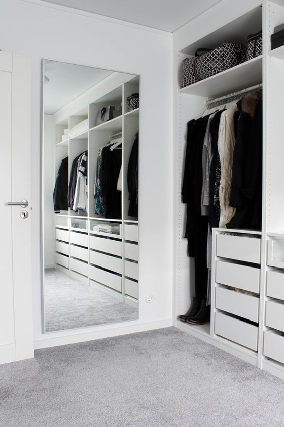 a minimalist white closet with built in drawers, open storage compartments and a large mirror