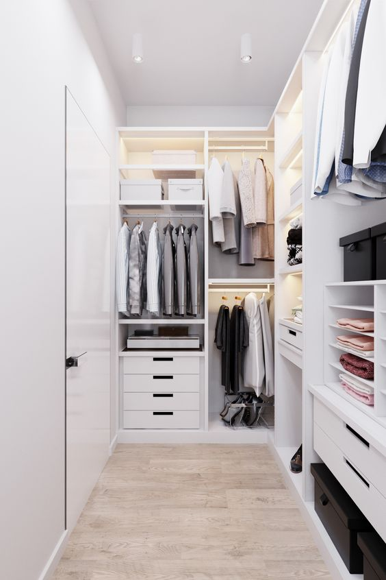 a minimalist white closet with lots of open storage compartments, drawers, shelves and built in lights