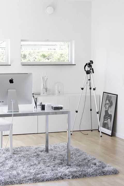 a minimalist white home office with a metal desk, a long sleek storage unit, an artwork and a fluffy rug