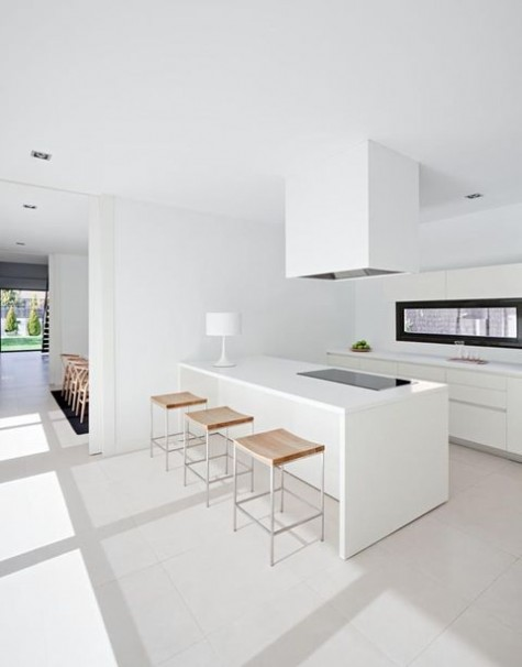 a minimalist white kitchen with sleek cabinets, a large hood and a kitchen island plus a cool long window backsplash for more light