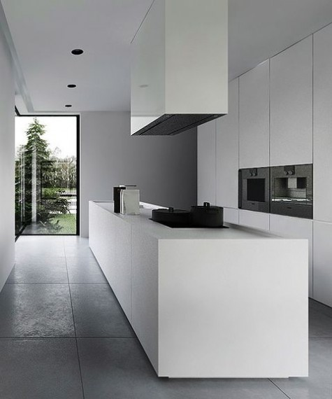 a minimalist white kitchen with sleek cabinets, a long kitchen island and a large hood plus black appliances built-in