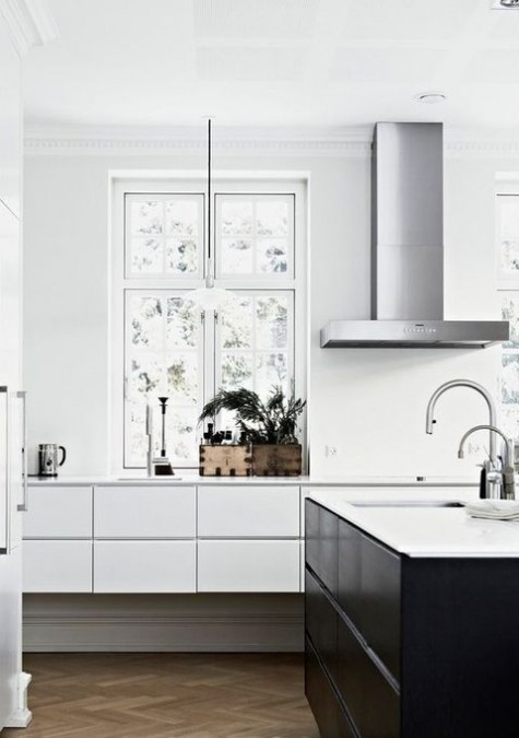 a minimalist white kitchen with sleek cabinets, a stone countertop, a black kitchen island and stainless steel fixtures