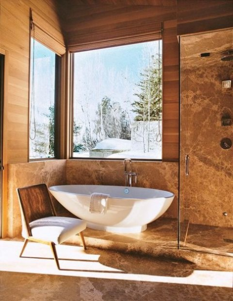 a mmodern chalet bathroom fully clad with stone in a warm shade, with a tub by the window, a shower space and a chair