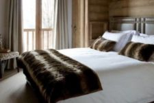 a modenr chalet bedroom clad with light-colored wood, with a leather bed, some upholstered furniture and faux fur