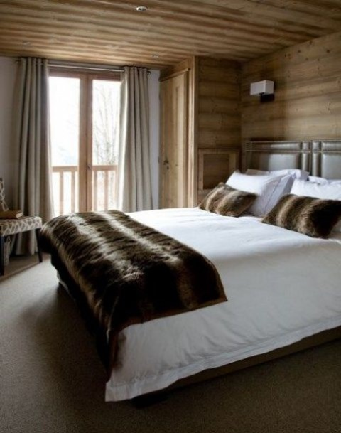 a modenr chalet bedroom clad with light colored wood, with a leather bed, some upholstered furniture and faux fur