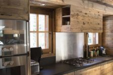 a modenr chalet kitchen with sleek no knob cabinets, black stone countertops, a wooden hood with storage and built-in appliances