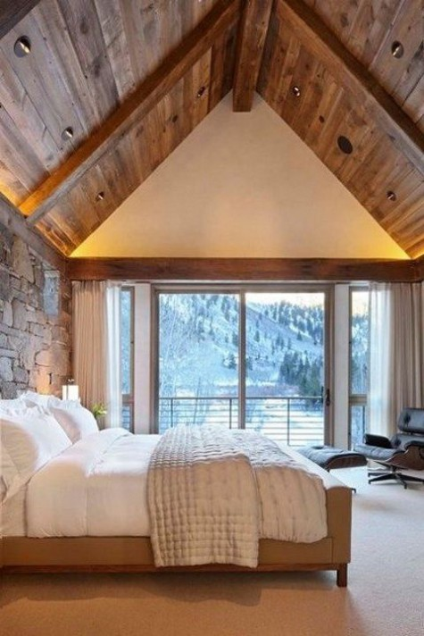 a modern and welcoming chalet bedroom with a glazed wall, comfy modern furniture and a stone accent wall