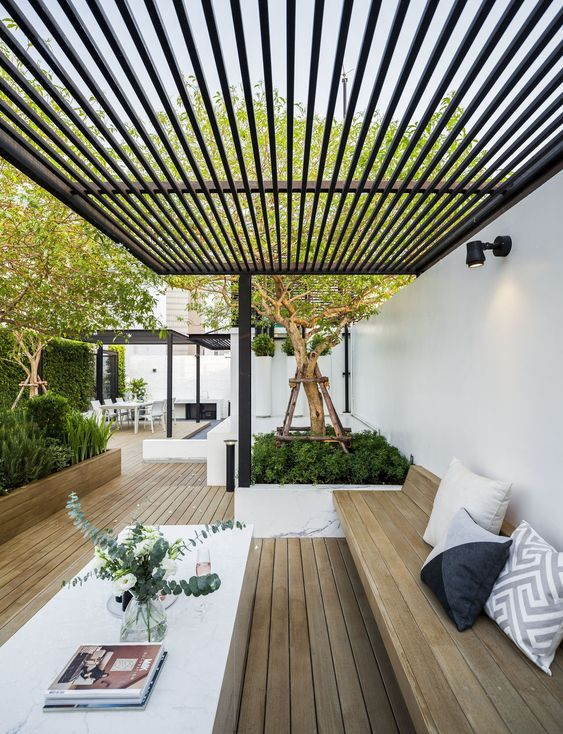 a modern backyard with a dining space, a built-in wooden bench and a white table plus lots of greenery planted