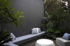 a modern backyard with long built-in bench, some greenery and trees, a chair and a white coffee table